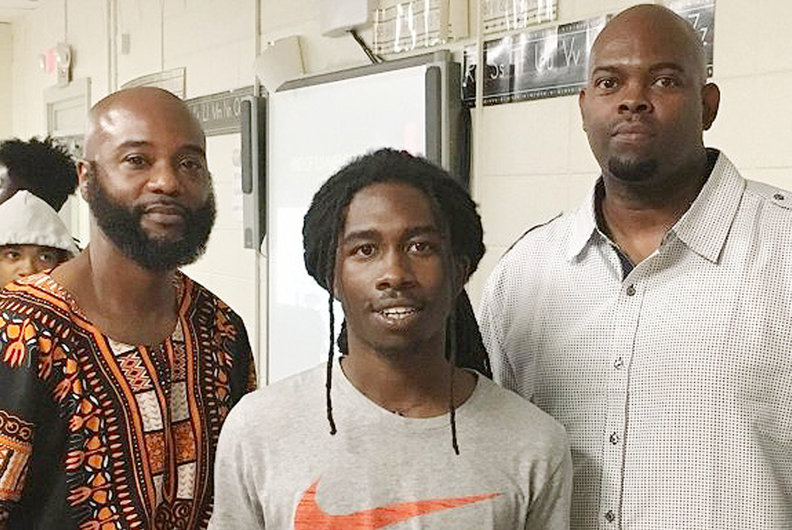 3 men standing together in a classroom