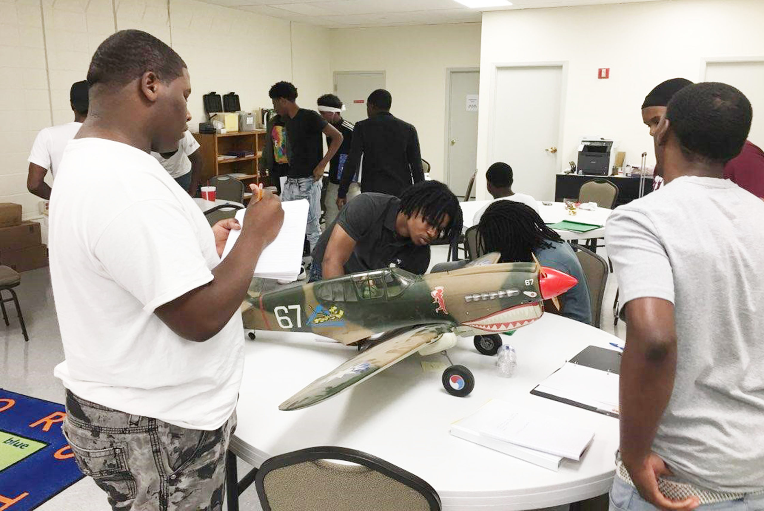 Students looking at a model airplane