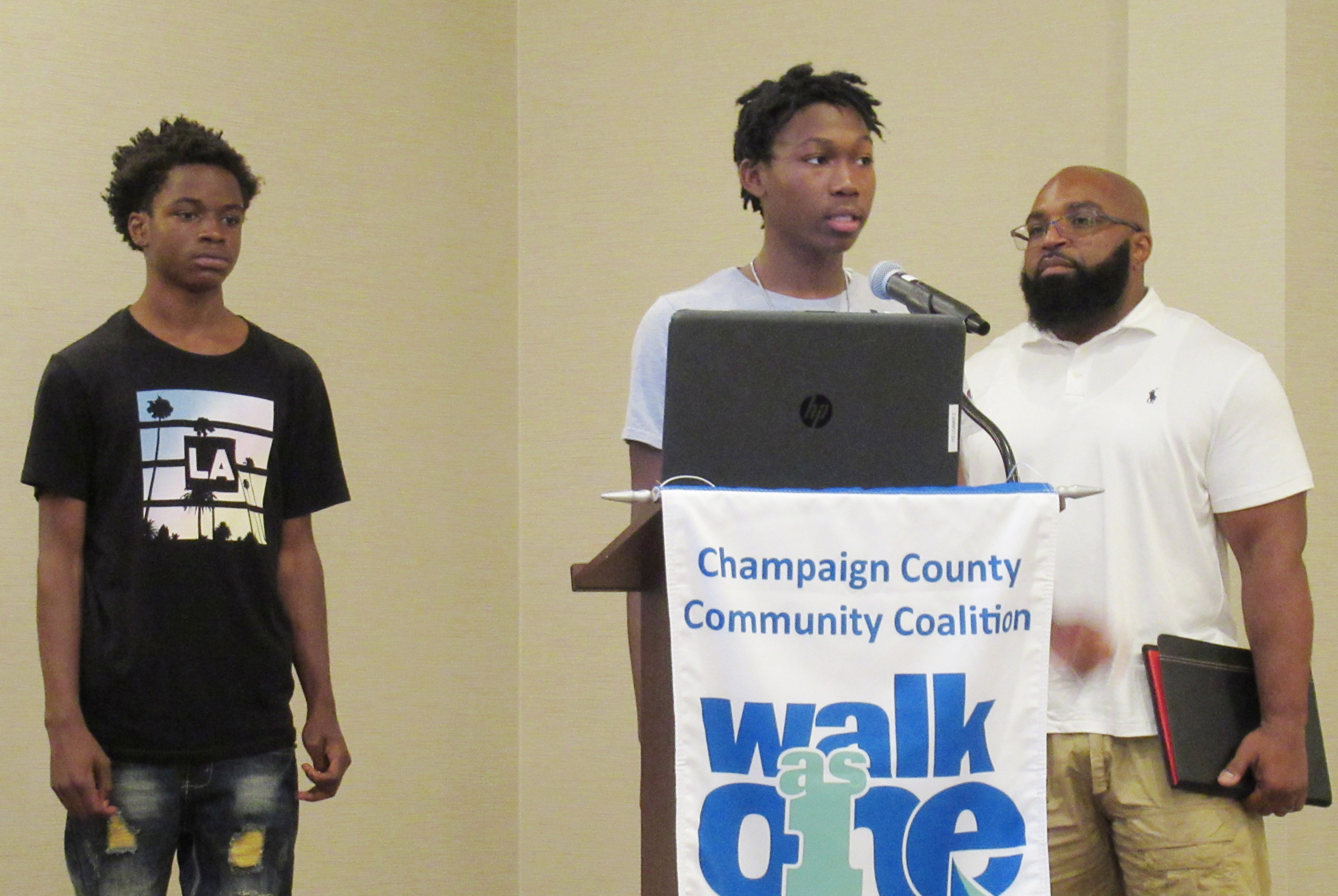 young men and adult at podium